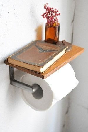 Hide the roll of toilet paper under a tiny shelf, perfect for some reading material and a vase.