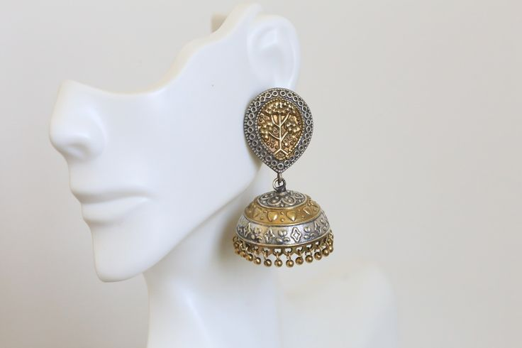 A pair of jaw dropping statement jhumka in two tone finish. Made with gold plated white metal , these earrings are exact replica of silver jhumka's at a very affordable price. Product details: Height