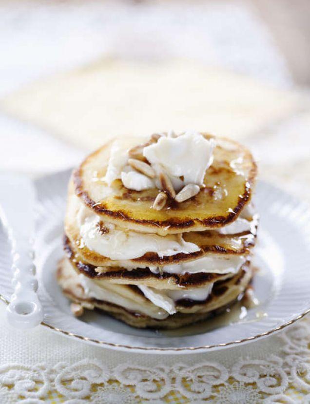Fluffiga pannkakor med syrlig getost, söt honung och knapriga pinjenötter är en given succé till frukost.