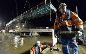 L'élargissement du pont Churchill a franchi un grand pas. La première des deux passerelles piétonnes a été installée. Une vingtaine d'hommes se sont affairés entre 21 h et 5 h du matin pour soulever cette plate-forme longue de 50 m et large de 1,5 m au-dessus des câbles aériens du tramway. Ils ont ensuite fixé la structure sur des piliers de 4,5 m ancrés au fond de l'Orne.