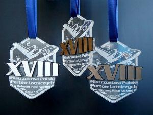 Medale sportowe na Mistrzostwa Polski Portów Lotniczych w halowej piłce nożnej. Medale z pleksi i laminatu.