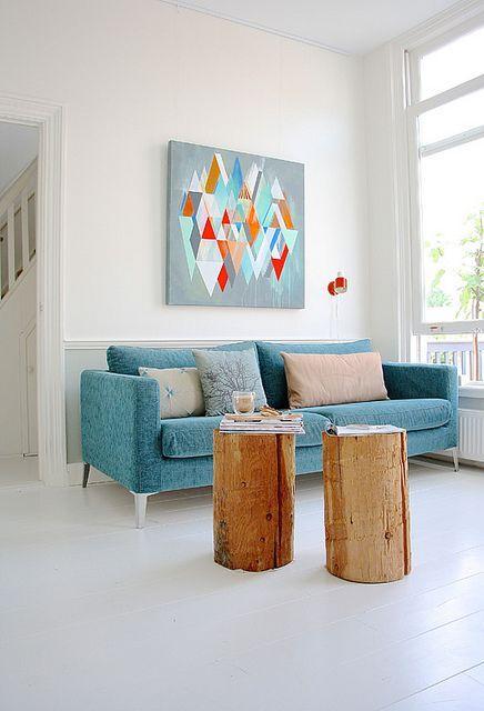 Living Room decor ideas - Simple, modern, scandinavian inspired. Bright aqua modern sofa, wood log tables, colorful art.