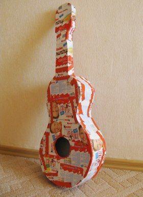 Для этого нам понадобится следующие ингредиенты: Киндер-шоколад – 11 упаковок (в каждой упаковке 8 маленьких шоколадок) Шоколад Киндер-кантри – 5 упаковок (в каждой упаковке 6 шоколадок) Плотный картон Толстые нитки или круглая тесьма На листах картина рисуем 2 одинаковых силуэта гитары, причем гриф одной гитары нужно сделать чуть подлиннее, чем у другой. Далее нужно склеить эти две гитары вместе через полосу картона, чтобы получилась «настоящая», объемная гитара.