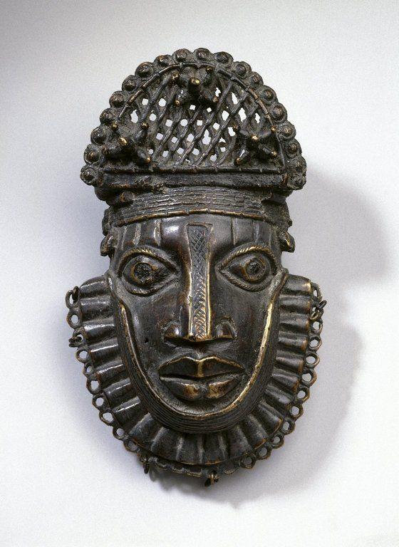 Hip Ornament with Human Face (Uhunmwun-ekue).      Culture: Edo.     Medium: Copper alloy, iron.     Place Made: Benin, Edo State, Nigeria.     Dates: 18th century (possibly).     Brooklyn Museum.