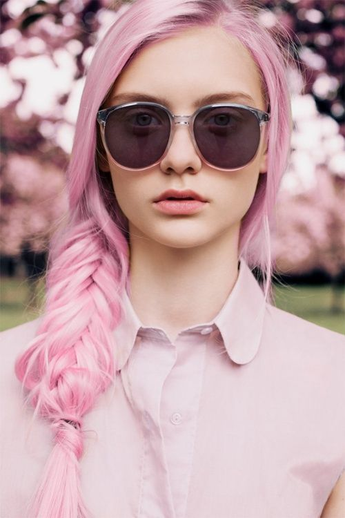 A fishtail braid with a pink collar top and a pair of long round sunglasses.