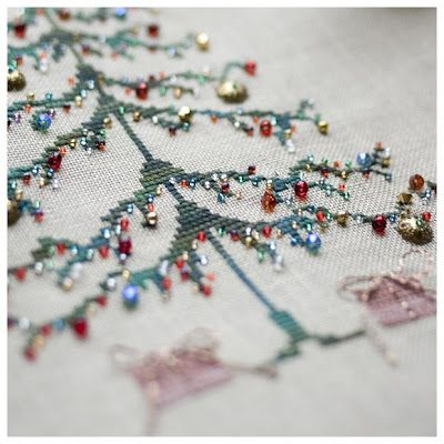 Cross stitch Christmas tree with tiny glass bead ornaments. So pretty!