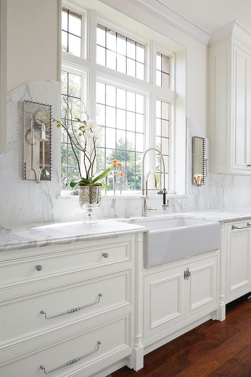 Exquisite kitchen features creamy white cabinets paired with grey and white marble countertops and a curved marble backsplash lined with mirrored wall sconces. A farmhouse sink and pull out faucet stands below windows.