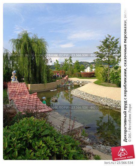 Декоративный пруд с корабликами, сказочные персонажи, зеленые деревья и кустарник, ландшафтный дизайн в Сочи Парке © DiS / Фотобанк Лори