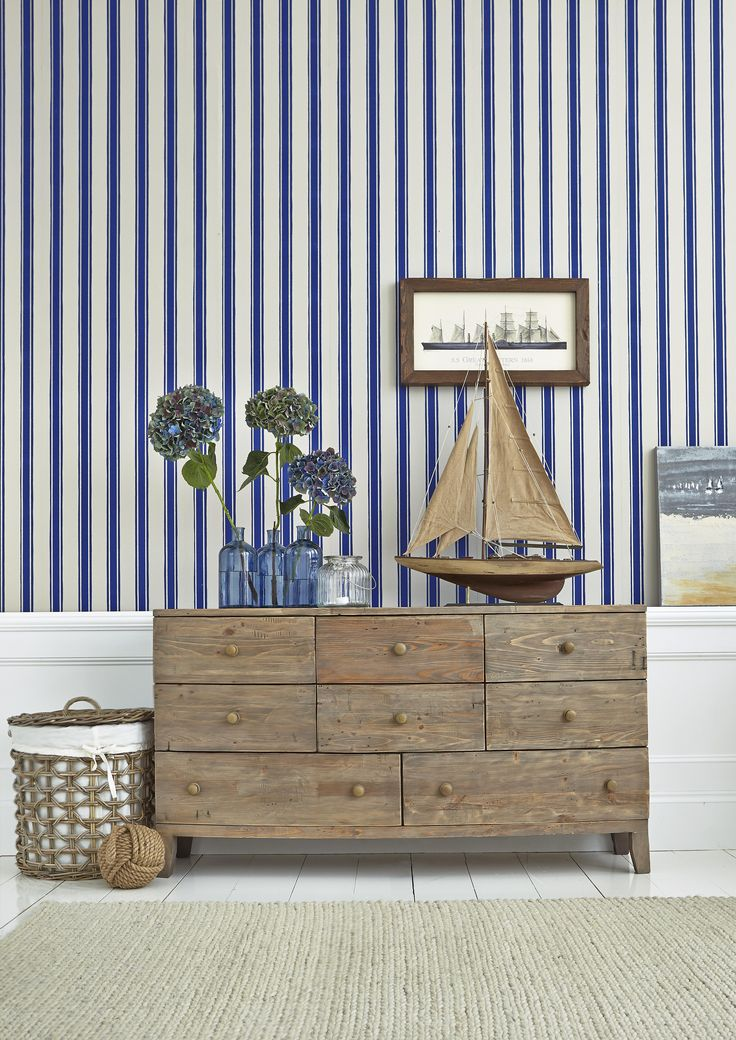 Blue striped wallpaper and rustic wooden sideboard = nautical decor in an instant
