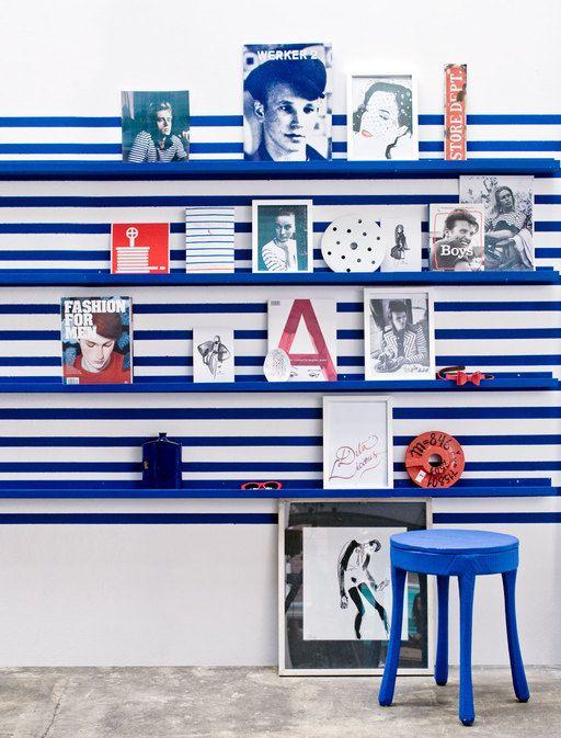 Een mini-galerie in huis springt extra in het oog als de ruimte tussen de schilderijplanken beschilderd is met een fris strepenpatroon.