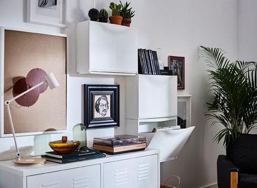 Uma parede de sala mobilada com três sapateiras TRONES alinhadas à volta de um móvel, para criar arrumação e pontos centrais
