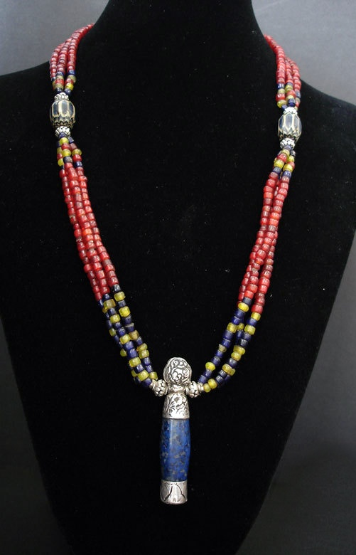 by Luda Hunter | 3 strands of old small Naga glass beads with a Nepalese lapis and silver seal pendant. The 2 large Nepalese blue and white chevrons are new contemporary beads and new Bali silver beads are added to the mix. | 165$