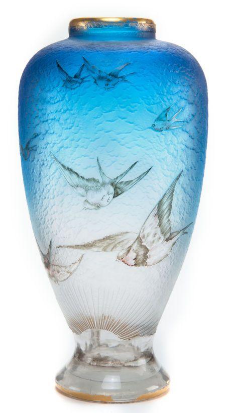 DAUM ETCHED AND ENAMELED GLASS HIRONDELLES VASE Sky blue glass with etched and enameled swallow motif, circa 1900 Signed: Daum (Cross of Lorraine) Nancy 8-1/4 inches high (21.0 cm) Estimate: USD 2,000 - USD 3,000