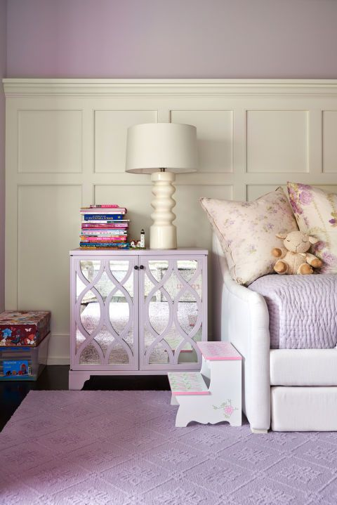 In a child's bedroom in Alec and Hilaria Baldwin's East Hampton home, creamy white wainscoting offers a sophisticated counterpoint to the more dainty lavender textiles found throughout the space. The mirrored purple nightstand is from Lillian August.