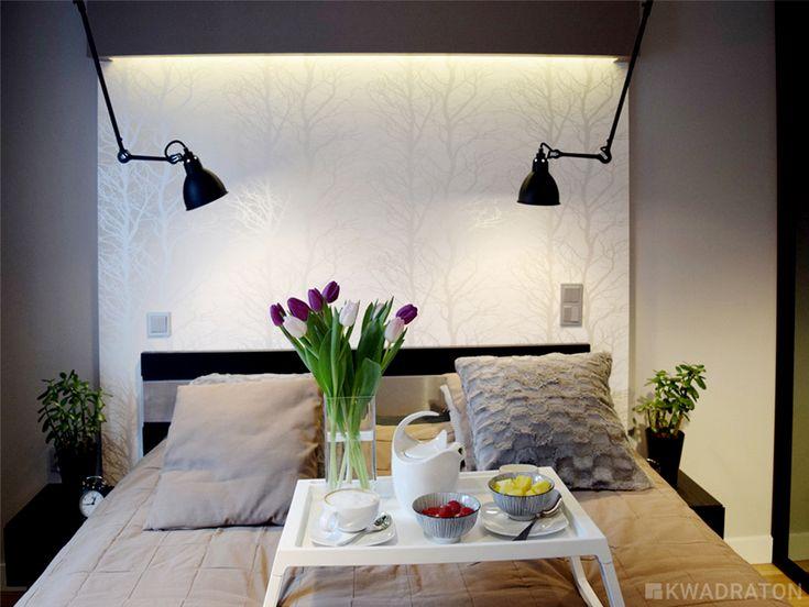 Przedścianka z płyty g-k z tapetą w połyskujące drzewa i montowane do sufity czarne lampy na ruchomym ramieniu.