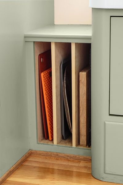 corner cabinet storage with slots for cutting boards and baking pans, retro style kitchen with soft green cabinets and salvage apron sink