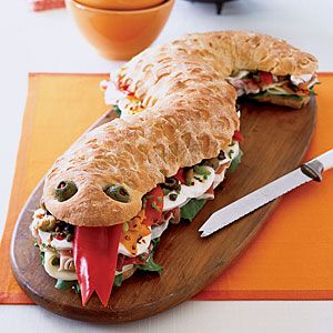 Snake Sandwich - uses 3 (1 lb.) loaves frozen bread dough, thawed shaped add olives for eyes and slice dough for scales, let rise 1 hour-  then bake at 350 for 30-40 minutes and let completely cool before cutting.  .... Choose your cheeses, veggies and lunchmeats or other sandwich filling. ... Add cut fresh red pepper or fruit roll-up for tongue.