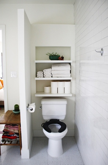 Shelves above a toilet, white on white with coves.