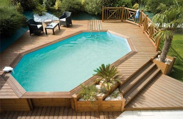 une grande piscine hors sol en bois sur la terrasse en bois