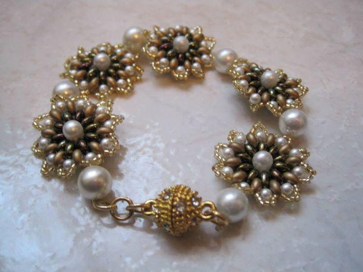 Bracciale floreale con perle bianche e Supeduo di colore oro e rame e conteria Miyuki di colore oro. Chiusura mategnetica dorata con strass.
