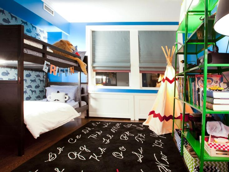 This kids' room has bookshelves, a graphic area rug, bunk beds, and vivid color.
