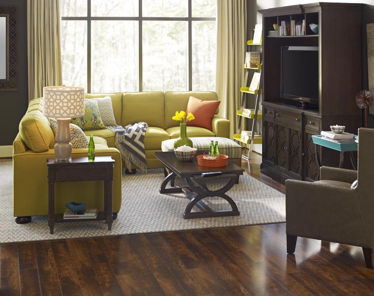 Dark walls and flooring envelope a custom corner sofa. The nirvana area rug delineates an intimate seating area.
