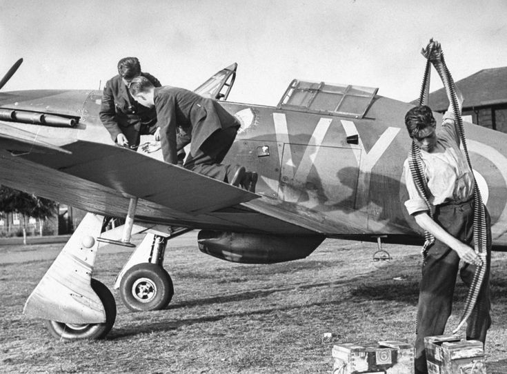 Battle of Britain, July-October 1940. The British Empire and its Commonwealth stand alone against Nazi Europe. Armourers load an RAF Hurricane with machine gun belts. Each of the Hurricane's eight .303 calibre machine guns received 300 rounds, enough for 15 seconds of firing.