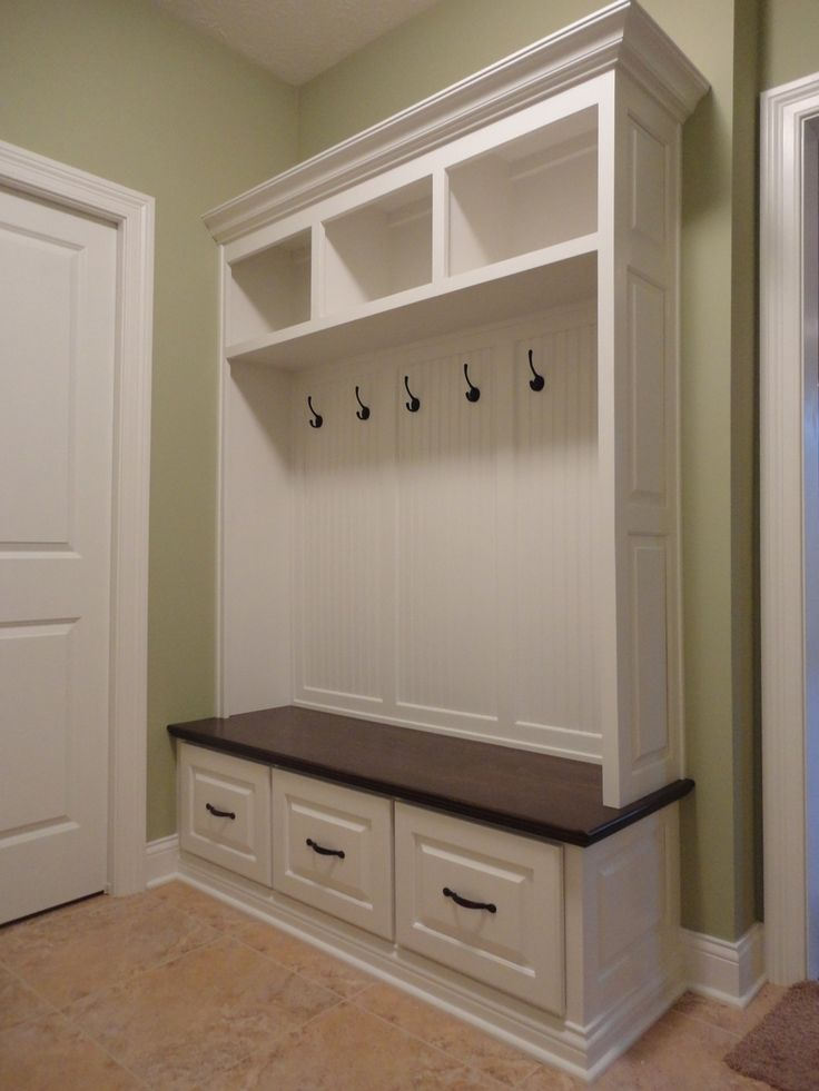 Entryway with white open storage lockers and shelf with hooks. Small wooden bench with small individual storage drawers. Cream - beige tiles on the floor.