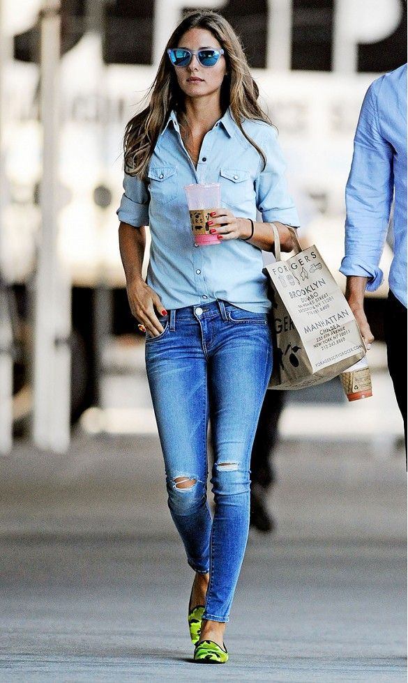 Olivia Palermo wears a light denim button-down shirt with distressed skinny jeans, mirrored sunglasses, and green flats
