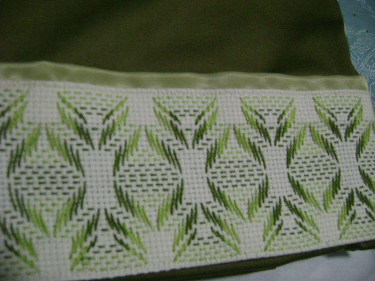 Un acercamiento para poder ver el detalle del bordado yugoslavo de estas fundas verdes.