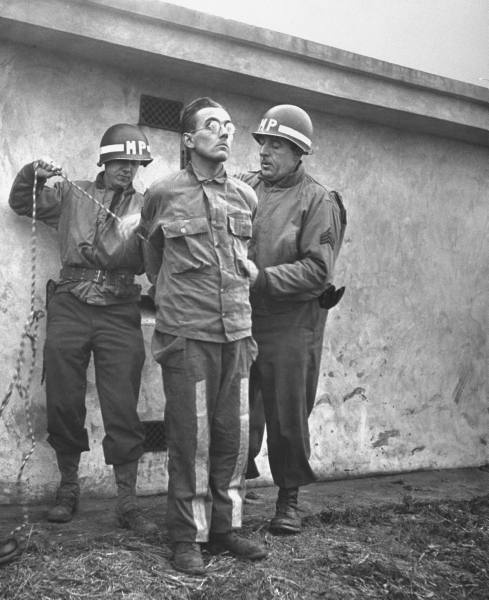 German commando Gunther Billing in US Army fatigues as US Army MPs tie his hands behind him before facing the firing squad. Billing was one of a group of German commandos who infiltrated US lines during the Battle of the Ardennes (Dec 1944) wearing US Army uniforms. Speaking fluent American English, the commandos proceeded to spread havoc and confusion in the rear. After their capture, most of them faced the firing squad.