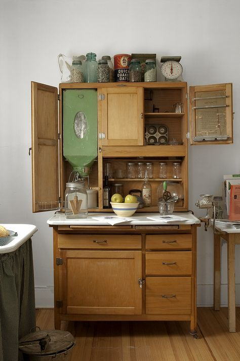 Here is the farm house kitchen cupboard, a fairly usual style in the early Twentieth Century. That is evidenced by the woof green flour bin and sifter. At least you can tell when you are running down on flour. That would still make a lot of sense in a modern kitchen when a lot of cooking goes on. Other items include legumes and rice on top. Some serious baking must have been done in the day if a kitchen scale was used. Old fashioned slow cooking oats are there. I am guessing the jar with…