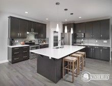 Open concept main floor and kitchen area. Dark-stained custom cabinets, light coloured quartz counters, modern pendant lighting. Onyx floorplan as built in Keswick on the River, by Kimberley Homes, Edmonton.  #interiordesign #newhomedesign #homedesign #newhome #customhome #yegre #buildwithkimberley #kimberleyhomes #kitchen #kitchenideas #kitcheninspo #kitchenreno