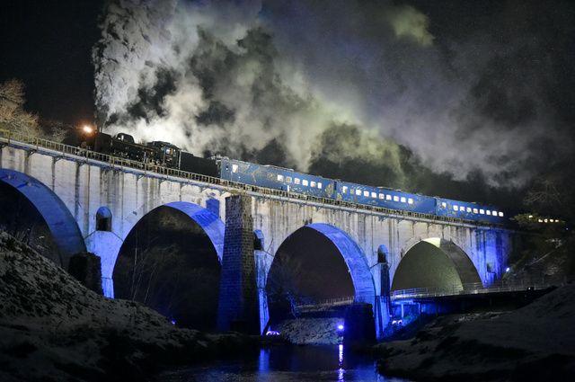 ライトアップされた「めがね橋」を走る特別運行の「SL銀河」=6日午後5時50分、岩手県遠野市