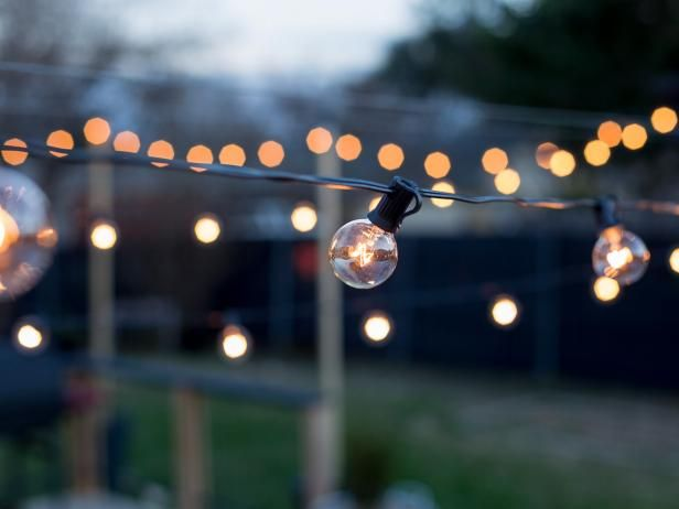 Café lights add a gorgeous glow to an outdoor living space, but they can be tricky to hang if you don't have trees or other tall objects to string them from. HGTV shows a freestanding solution for hanging lights using planters and wood posts.