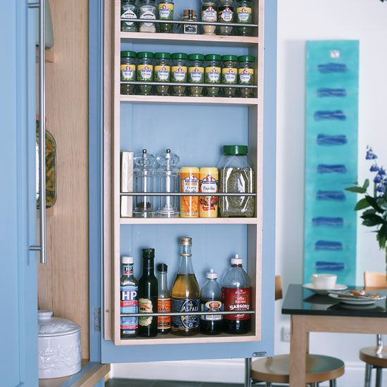 Small kitchen with white walls, blue cabinetry and built-in spice rack