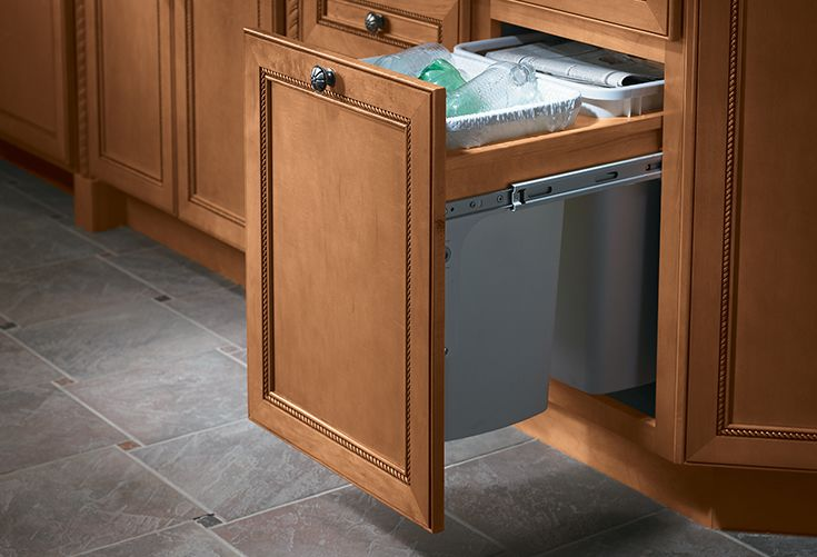 Choose form over function with Merillat pull-out trash bins that provide a stylish way to store trash and recycle items.