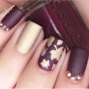 Elegant Autumn leaf nail design in golf and wine polish