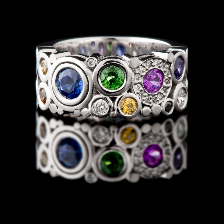 18ct white gold multi-coloured ring from our 'Carbonated' collection. Set with blue, yellow and purple Sapphires, Diamonds and Tsavorite garnet. This ring is just gorgeous. #CaratsJewellery