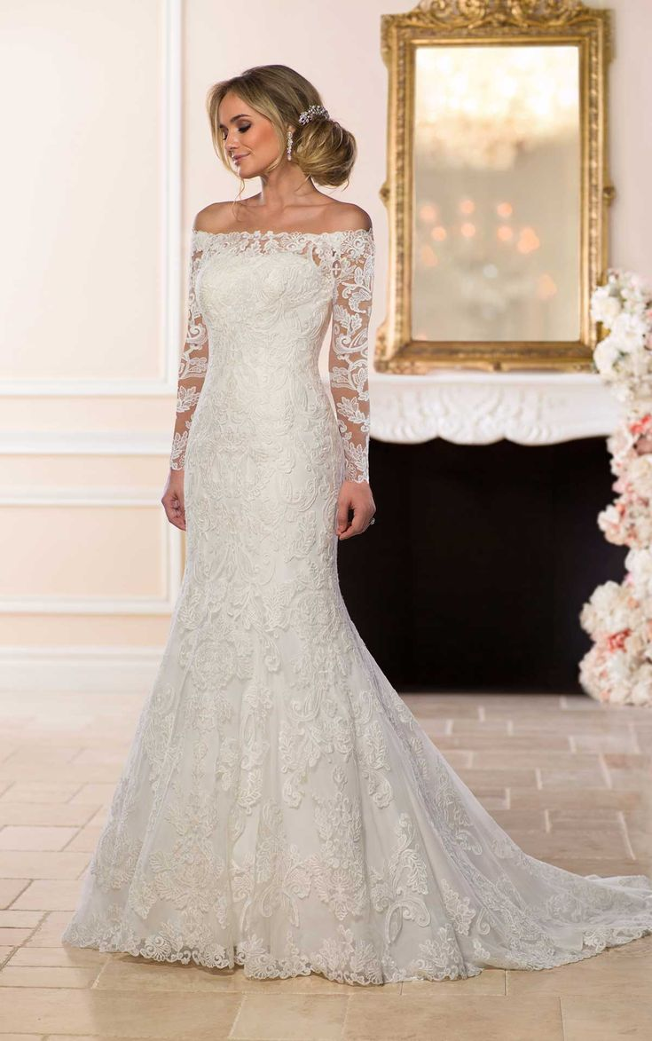 Off-the-shoulder, long lace sleeves and a classic silhouette come together in this masterpiece from designer Stella York. Lace and tulle create a fit-and-flare silhouette with a modern neckline that shows off the bride?s shoulders and focuses on the off-the-shoulder sleeves. Rich, matte lace in a fun and flirty floral pattern makes this wedding dress look and feel very luxurious, while a low cameo-style lace back adds a touch of modernity. A long, floral lace cathedral train adds a classic…