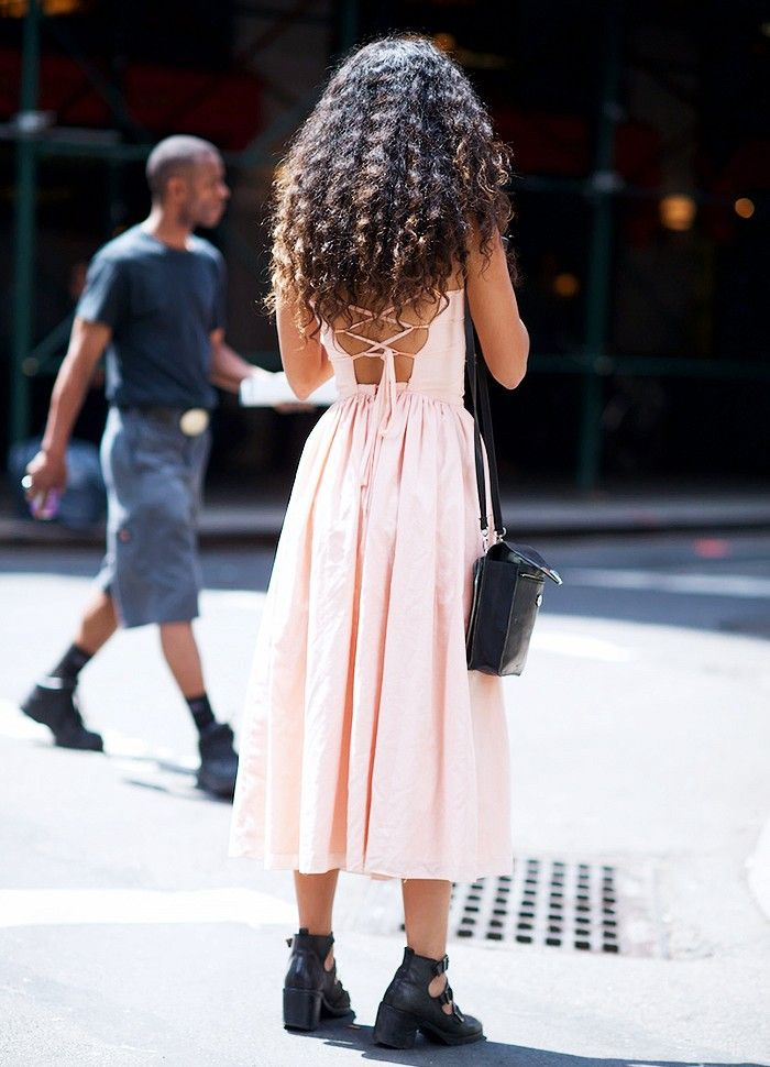 A feminine lace-up dress is paired with cool buckle boots and a black bag