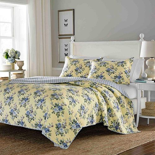 This Laura Ashley quilt set sports a yellow and blue floral print.  This quilt is fully reversible to a striped back.
