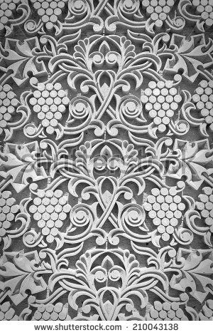 Ornament from grapes, grape leaves, lines and patterns handmade decorating the wall of the church in monochrome - stock photo