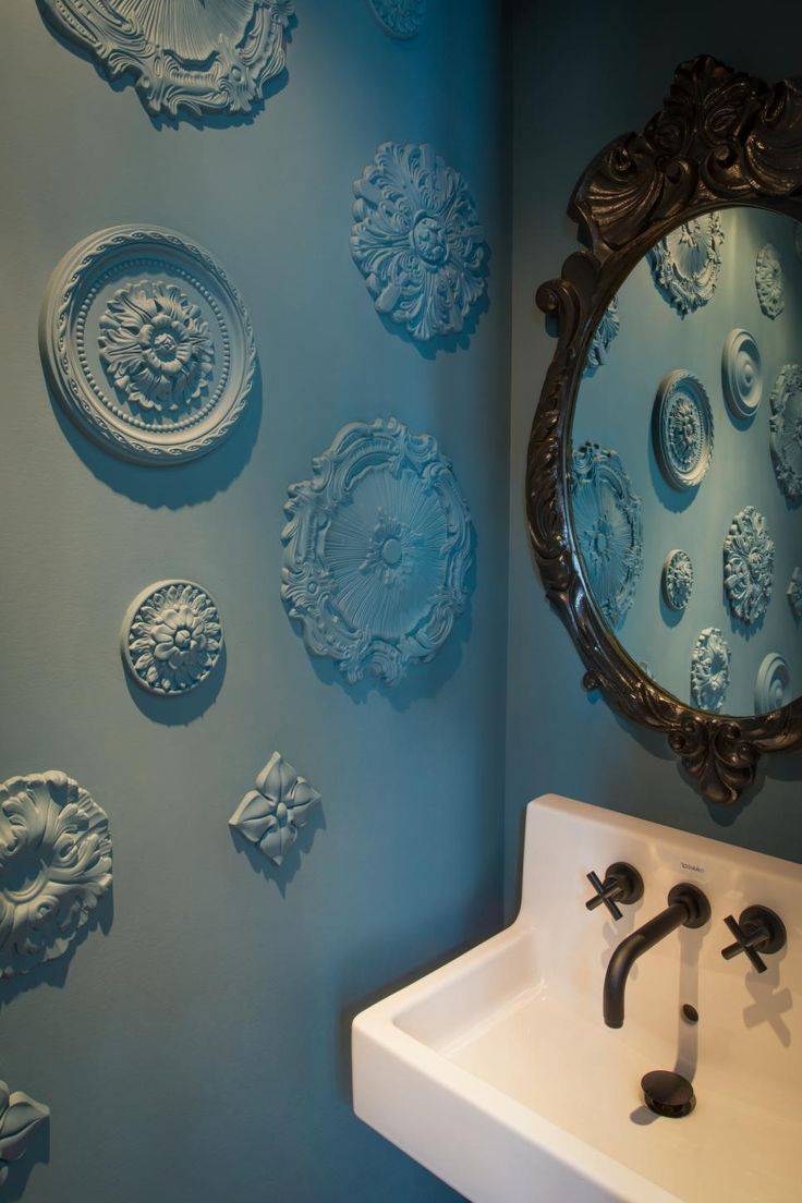 Plaster medallions add an unexpected touch of texture in this blue traditional powder room.