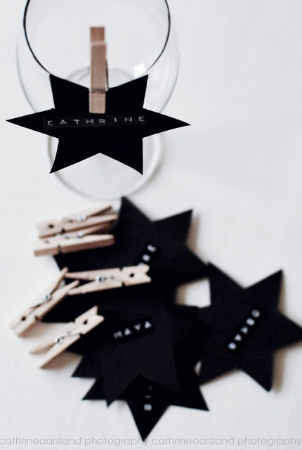 Place setting: black cardboard star with name embossed on black tape with a vintage label maker. Atttach the star to a glass with a tiny clothes pin. Could also use a neon tape or write with a white marker.