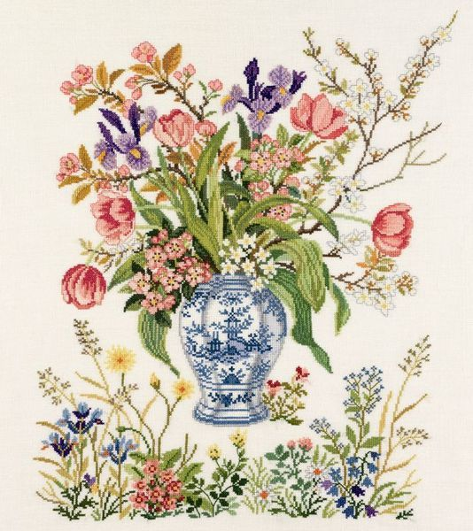 A lovely floral picture with a vase of garden flowers and colourful wild flowers in the foreground.