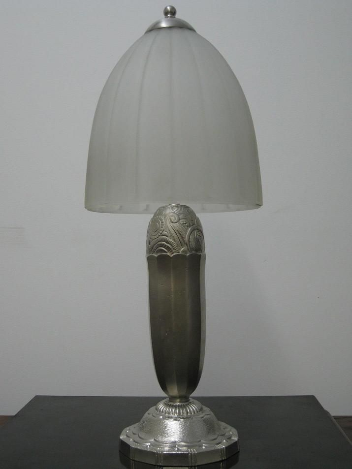 Pair of French Art Deco Table Lamps - A stunning Pair of French Art Deco Table Lamps in clear frosted molded Glass Shades with ribbed lines and polished details. The stem and base are enhanced with flower & geometric motif in satin Nickel Bronze. Re-plating available upon request.  Reference #: TL8709  Measurement: Height: 21.5 in. (54.61 cm) Diameter: 8 in. (20.32 cm) Shade Height: 9 in. (22.86 cm) Diameter: 8 in. ( 20.32 cm)
