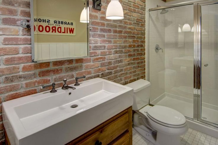 Modern basement bathroom with red brick accent wall on for Red accent bathroom