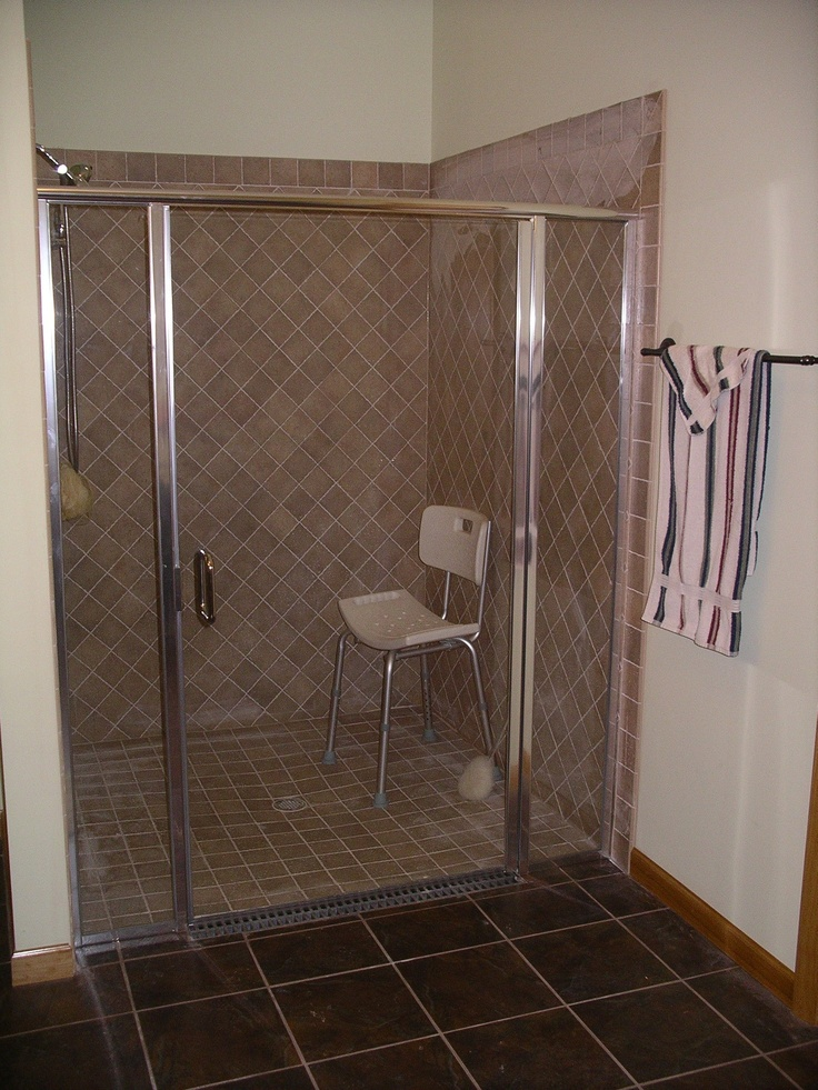 handicap accessible tile shower with glass doors completed by