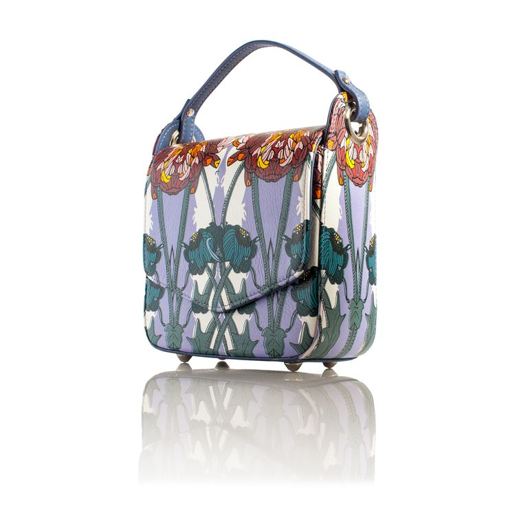 COMING SOONA flower Moment, Cross-body handbag, featherlight We never do florals but we had a dream. Large imposing wild flowers wrapping there petals around your bag. So a flower moment was born. We combined loud purples with hits of baby pink, orange and maroon reds all on a background of white and petrol blue.  INFORMATIONThe perfect small structured leather cross-body, leather handbag . Comes with a detachable  body strap and a permanent handle .The inside is v...
